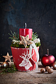 Festive arrangement with red candle in flower pot decorated with white stag's head