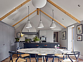 Large, round marble dining table and open-plan kitchen in living space on gallery