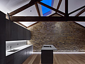 Modern monochrome kitchen with island counter in restored brick house