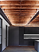 Modern monochrome kitchen with wood-beamed ceiling in restored brick house