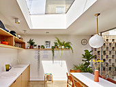 Light-flooded, open-plan kitchen with skylight and glass wall overlooking courtyard garden