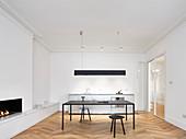 Offener Wohnraum modern minimalistisch eingerichtet mit Küchenzeile, Tisch und Kamin