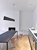 Kitchen counter, table and fireplace in modern minimalist interior