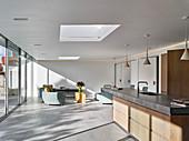 Offener moderner Wohnraum lichtdurchflutet durch Glasfronten und Oberlichter