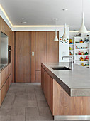 Designer kitchen with wooden cabinets and concrete worksurface on island counter