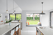 Modern kitchen-dining room with window seat overlooking garden