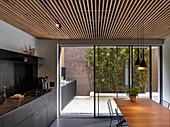 Modern kitchen counter continuing onto courtyard terrace