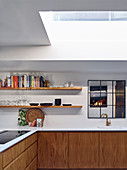 Modern kitchen with wooden cabinets and skylight