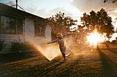 Kind rennt durch den Rasensprenkler bei untergehender Sonne