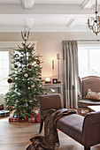 Beige chaise longue and Christmas tree in living room