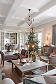 View across coffee table to Christmas tree in living room with coffered ceiling