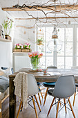 Grey shell chairs around wooden table in dining room with spring decorations