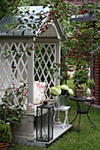 Philosopher's bench with lantern and hydrangea in a zinc pot