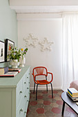 Orange chair below star-shaped lamps on wall and next to sideboard