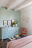 Pale blue chest of drawers against duck-egg-blue wall in bedroom with white ceiling beams