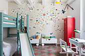 Bunk beds with slide and wallpaper with map of the world in children's bedroom