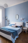 Bedroom in shades of blue with herringbone parquet floor in period building