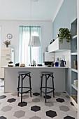 Barstools at counter in open-plan kitchen with honeycomb floor tiles