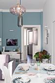 Offener Wohnraum mit Wohn- und Essbereich in kühlen Farben