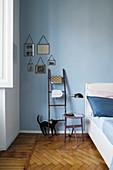 Leiter als Ablage und Nachttisch vor blauer Wand im Schlafzimmer