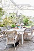 Wooden table and rattan armchairs on terrace