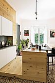 Modern, open-plan wooden kitchen with Italian tiled floor