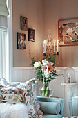 Glass vase of flowers next to pale blue sofa with scatter cushions