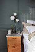 Bedside table with marble top against blue wall in bedroom