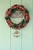 Christmas wreath on green wooden door