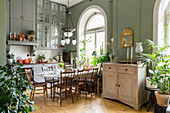 Dining table, houseplants, green walls and arched windows in kitchen with high ceiling