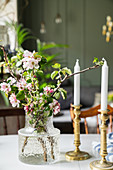Glass vase of flowering branches and candles on dining table