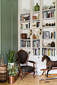 Floor-to-ceiling shelving, antique chair and rocking horse in living room