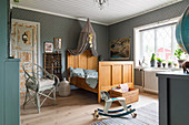 Antique wooden bed with crown, chair and rocking horse in child's bedroom