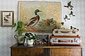 Vintage suitcases on antique cabinet in front of poster with duck motif