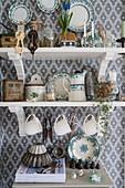 Regale mit Geschirr vor tapezierter Wand in Landhausküche