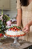 Strawberry cake on glass cake stand