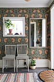 Two chairs below mirrors on wall with William Morris floral wallpaper in hallway