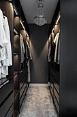 Walk-in wardrobe with dark cabinets and pale carpet