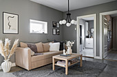 Pale sofa and coffee table in living room with grey walls