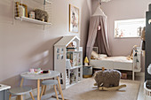 Dolls' house and bed with canopy in girl's bedroom with matt pink walls
