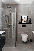 Shower cubicle in bathroom with grey tiles