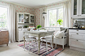 Antique, white-painted furniture, patterned wallpaper and rag rug in dining area