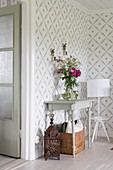 Flowers on console table and table lamp on stool against patterned wallpaper
