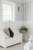Bench in foyer with white wainscoting and pretty wallpaper