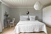 Weißer Kleiderschrank, Doppelbett und Schreibtisch im Schlafzimmer mit Tapete