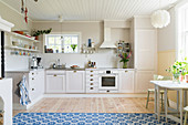 Bright kitchen with board floor and blue-and-white rug