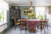 Wooden table and chairs and painted, antique corner cabinet in dining room