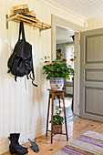 Plant stand in hallway with white-painted, wood-clad walls
