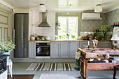 Grey cabinets in country-house kitchen with antique table in foreground