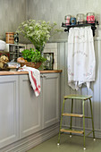 Grey cabinets, step stool and shelf in country-house kitchen